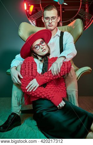 Handsome young man hugs beautiful young woman, sitting on an armchair in a luxury apartment, dating. Glamorous lifestyle. Fashion shot.