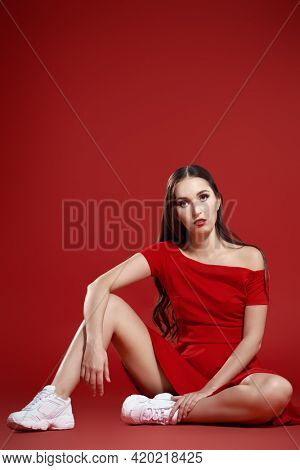 Beautiful brunette girl posing at studio in red dress and white sneakers. Red background. Sport chic style.