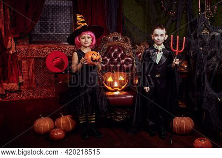 Halloween party. Happy cheerful kids in carnival costumes having fun on Halloween in the old castle. Trick or treat.