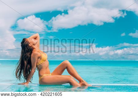Asian bikini model sexy woman relaxing by the swimming pool sunbathing in yellow swimsuit. Closed eyes enjoying the sun tanning with healthy long hair, skincare spa.