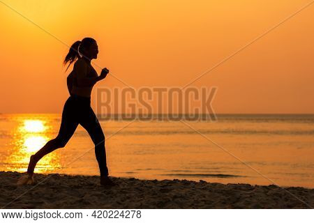 Silhouette Athletic Woman Jogging And Relax And Freedom On Sand Beach. People Running And Workout In