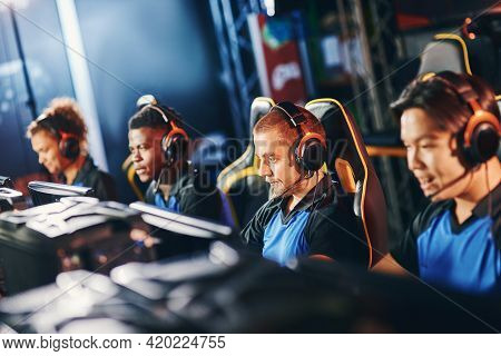 Team Of Four Professional Cybersport Gamers Wearing Headphones Participating In Esport Tournament, P