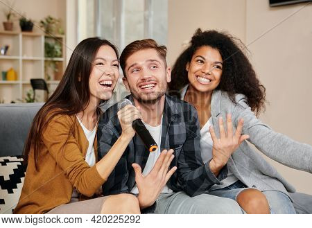 Karaoke Singers. Three Smiling Friends Looking Happy While Playing Karaoke At Home, Singing With Mic