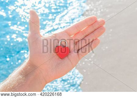 In The Hand Of A Man On The Palm Of A Small Red Heart Close-up In The Form Of A Lock. A Sign Or Symb