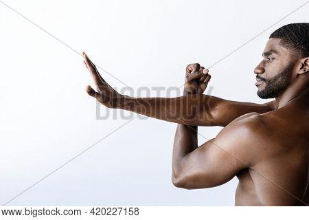 Naked black man warming up before exercise