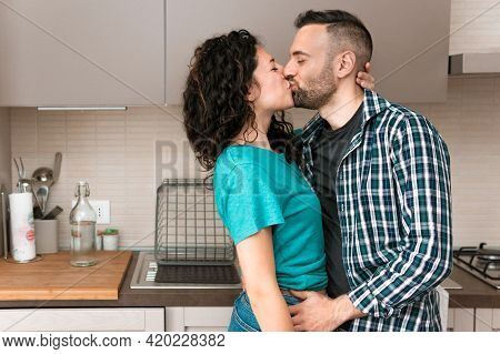 Romantic Engaged Couple Is Kissing In The Kitchen Of Their New Home - Concept Of Romance And Happine