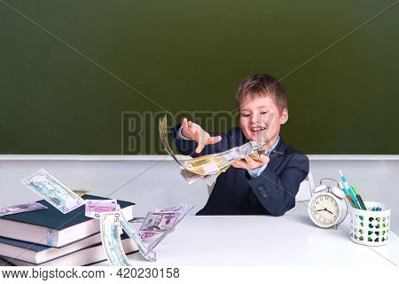 Junior Boy In A School Uniform At A Desk With Money In Dollars And Euros