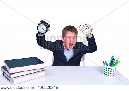 Junior In School Uniform At A Desk With Books And Alarm Clocks In His Hands, Isolated On A White Bac