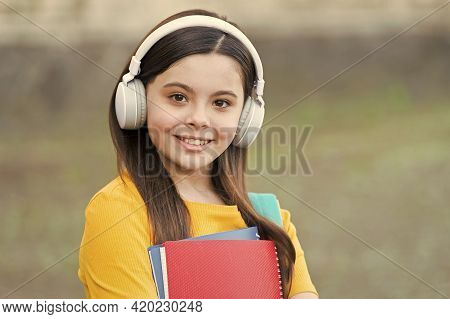 Check Out New Music. Happy Child Listen To Music Outdoors. Little Kid In Headphones Hold Printed Mus