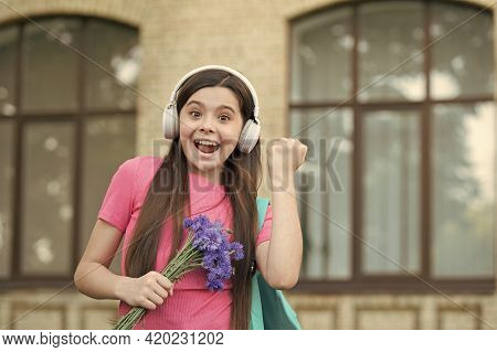 Right Way To Celebrate. Happy Child Make Winner Gesture. Little Girl Hold Flowers Listening To Music