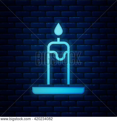 Glowing Neon Burning Candle In Candlestick Icon Isolated On Brick Wall Background. Cylindrical Candl