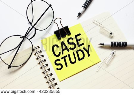 Case Study. Sticker Attached To A Notebook On A White Background Near Beautiful Glasses
