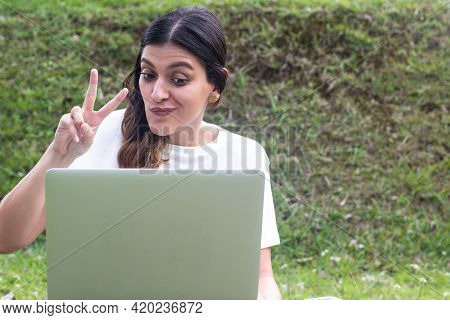 Latina Sits At A Laptop At Campus And Works In Isolation, And Shows Peace Sign At The Camera. Fresh