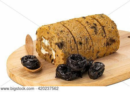Closeup View Sliced Prune Sponge Cake Roll, Dried Pitted Prune In Wooden Board And In Wooden Spoon O