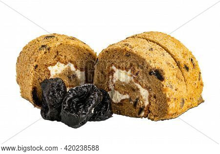 Side View Of Sliced Homemade Prune Sponge Cake Roll And Pile Of Dried Pittrd Prune On White Backgrou