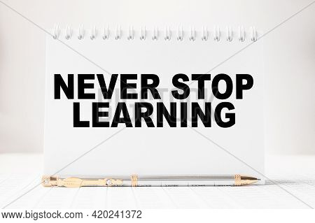 Notepad With Text Never Stop Learning On The Office Desk With Stationery. A Blank Notepad For Enteri
