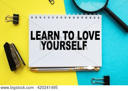 A Notepad With Text Learn To Love Yourself On The Office Desk With Stationery. A Blank Notepad For E