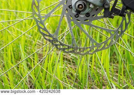 Side View Of The Spokes And Brake Disc Of A Mountain Bike On A Green Grass Background. Healthy Lifes