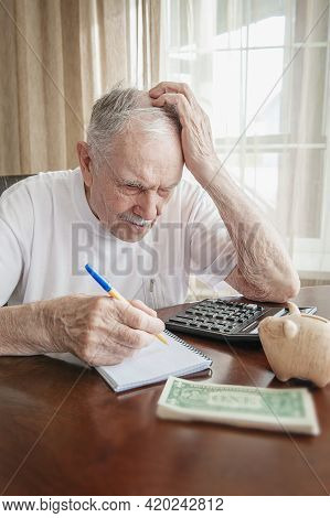 Old Man In A Depression Is Counting Pennies From The Pension Fund. A Worried Elderly Man Saves Money