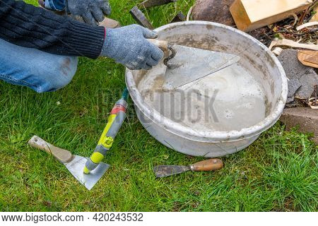 Hands Cleaning Trowels After Finished Masonry Works