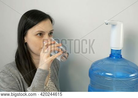 Woman Is Pouring Water Into Glass From An Automatic Water Cooler And Drinking It. She Is Pouring Fre