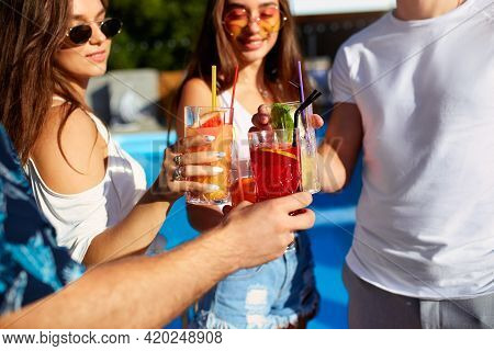 Close View Of Friends Having Fun At Poolside Summer Party, Clinking Glasses With Fresh Summer Cockta