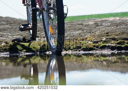 Bicycle Wheel In A Puddle. The Bike Moves Through The Puddles On A Rainy Day. Close-up