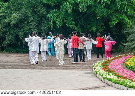 Chongqing, China - May 9, 2010: Group Of People In Silver, Blue And Red Silk Outfits Practicing Sync