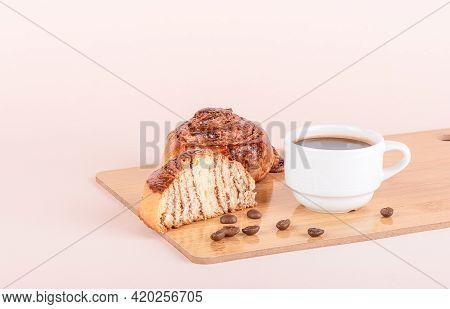 White Cup With Coffee, Whole Cinnamon Bun And Half Bun On A Cutting Board.
