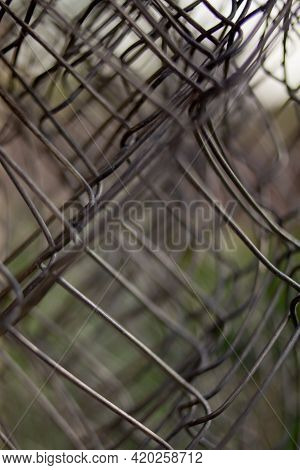 Twisted Mesh. Welded Wire Mesh Twisted Into A Roll Background. Fence Stretched Mesh Background. Mesh