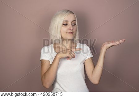 Beautiful Young Blonde Woman In A White T-shirt On A Pink Background Shows A Finger. Place For Text,
