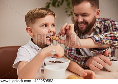 Little Boy Biting Yummy Cookie Held By Smiling Dad While Having Breakfast Together In Morning