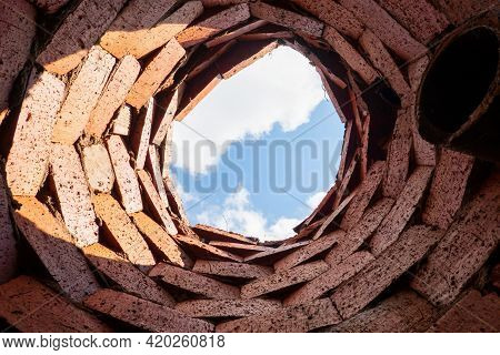 A Look Up From A Primitive Drainage Well. The Walls Are Made Of Rough Plain Bricks And There Is A Dr