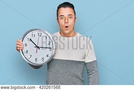 Handsome young man holding big clock scared and amazed with open mouth for surprise, disbelief face