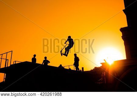 Unrecognizable Teenage Boy Silhouette Showing High Jump Tricks On Scooter Against Orange Sunset Sky