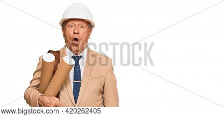 Senior caucasian man wearing safety helmet holding blueprints scared and amazed with open mouth for surprise, disbelief face