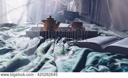 Image Of A Wooden Tray With A Coffee Pot And Mug Sitting On An Unmade Bed. On The Bed Is An Open Boo