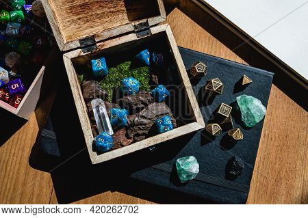 Image Of A Wooden Box With Blue Role-playing Game Dice On Top Of A Black Notebook With Green Crystal