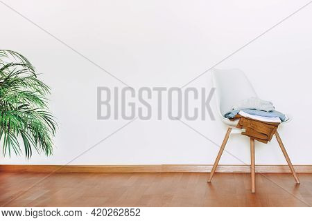 Indoors Flat Wall Mockup With Green Potted Houseplant And Chair With Clothes In Minimalist Style. In