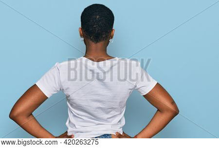 Young african american woman wearing casual white t shirt standing backwards looking away with arms on body