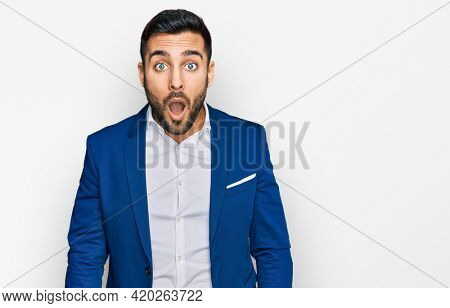 Young hispanic man wearing business jacket afraid and shocked with surprise and amazed expression, fear and excited face.