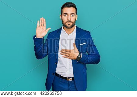 Young hispanic man wearing business jacket swearing with hand on chest and open palm, making a loyalty promise oath