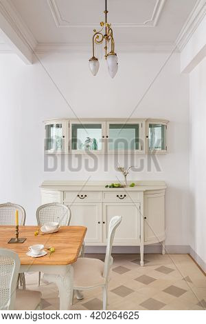 Front View Of Vintage Style Dining Room With Wooden Table Setting For Two Persons, Tile Floor And Re