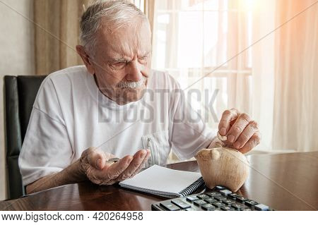 Old Man In The Pandemic Counts Pennies From The Pension Fund. Concerned About Lockdown, An Elderly M