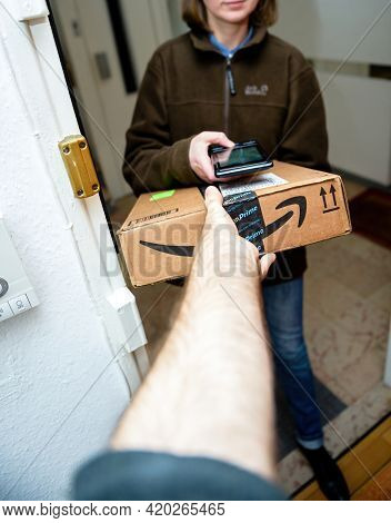 Paris, France - Jan 27, 2016: Male Hand Taking Through The Open Door The Cardboard Parcel From Amazo
