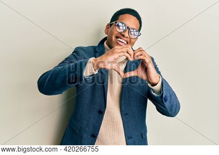 Young handsome hispanic man wearing elegant clothes and glasses smiling in love doing heart symbol shape with hands. romantic concept.
