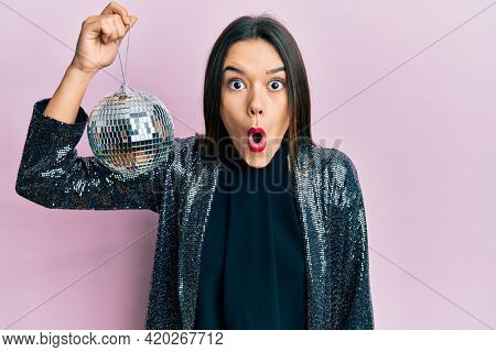 Young hispanic girl holding shiny disco ball scared and amazed with open mouth for surprise, disbelief face