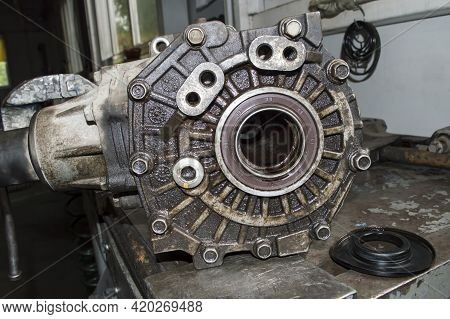 Side View Of The Transfer Case Removed From The Car Which Lies On The Desktop In The Auto Repair Sho