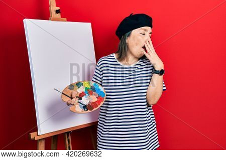 Middle age hispanic woman standing drawing with palette by painter easel stand bored yawning tired covering mouth with hand. restless and sleepiness.