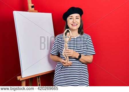 Middle age hispanic woman standing by painter easel stand holding manikin looking positive and happy standing and smiling with a confident smile showing teeth